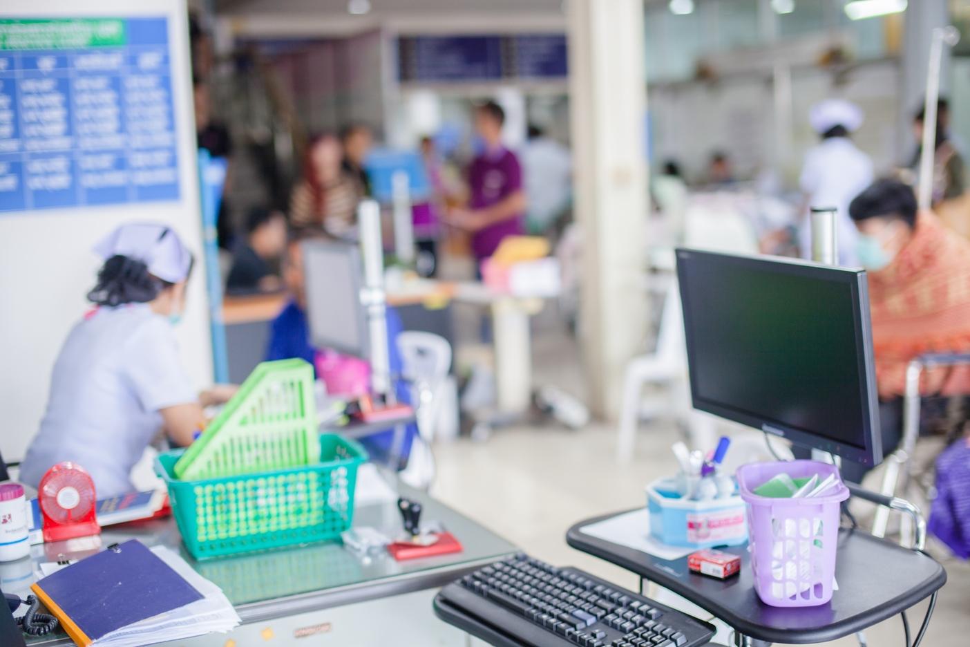 Bulanık bir resim içinde hastalar sırada bekliyor sağlık çalışanları hastalara destek veriyor.