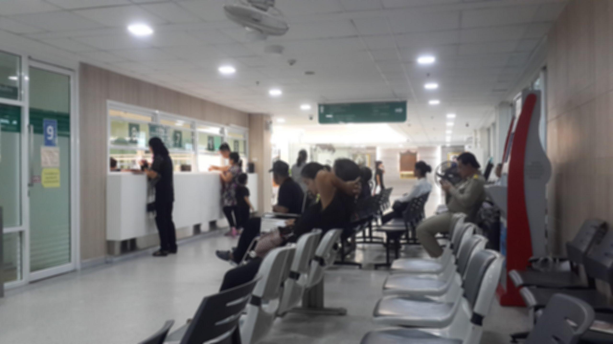 Hastalar hastane içinde sandalyelere oturmuş sıra bekliyorlar.