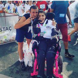 CP'li Büşra Ersoy maraton yarışları sonrası yanındaki erkek gönüllü ile zafer işareti yapıyor.