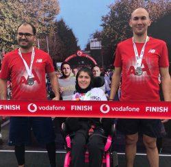 CP'li Büşra Ersoy maraton yarışları sonrası yanındaki 2 erkek gönüllülerle ile madalyaları boyunlarında yan yana duruyorlar.