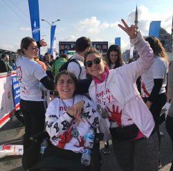 CP'li Büşra Ersoy maraton yarış alanında yanındaki kadın gönüllü ile zafer işareti yapıyor.