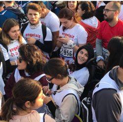 CP'li Büşra Ersoy maraton yarış alanında kalabalık gönüllüler arasında kuş bakışı yukarıya doğru bakarken gülümseyen anı.