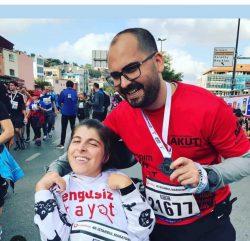 CP'li Büşra Ersoy maraton yarışları sonrası yanındaki erkek gönüllü ile madalyalı gülümseyerek poz veriyorlar.