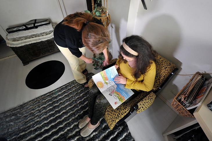 Koltukta oturan Neslihan Köse annesiyle beraber resimli hikaye kitabına bakıyor.