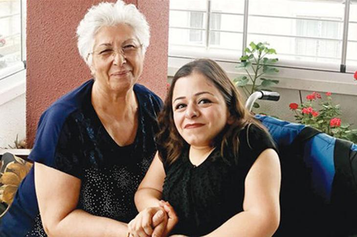 Cam kemik hastası Ceren Pekoğlu annesinin elini tutarak poz verirken.