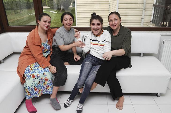 Solda serebral palsili üçüz kardeşler sağda anne Sinem Ersoy yan yana oturuyor.