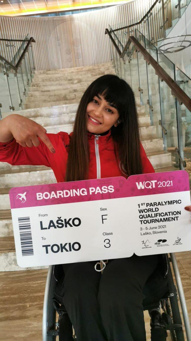 Paralimpik Masa Tenisi Milli Sporcumuz Nergiz Altıntaş elinde büyük boyutlu Tokyo Paralimpik Oyunları biletini mutlulukla gülerek tutuyor.